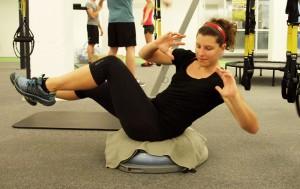 Bewege den Oberkörper diagonal zum leicht angezogenen Knie. Im Wechsel links und rechts